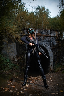 Kobieta w czarnym garniturze i masce gazowej z karabinem maszynowym w rękach.