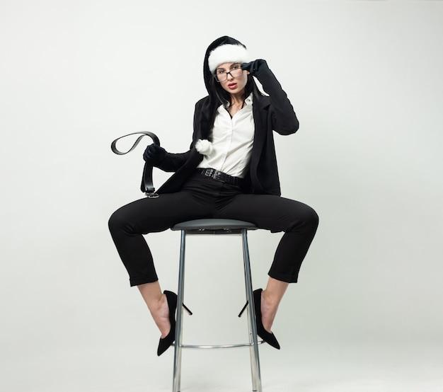 Kobieta w czarnym garniturze, okularach i czarnej czapce mikołaja ze skórzanym paskiem w dłoniach