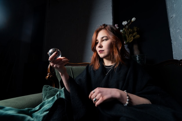 Kobieta w czarnym garniturze, trzymając w rękach kryształową kulę