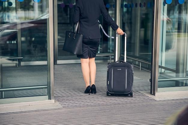 Kobieta w czarnym garniturze ze spódnicą niosąca walizkę podróżną podczas przechodzenia przez drzwi wejściowe na lotnisku