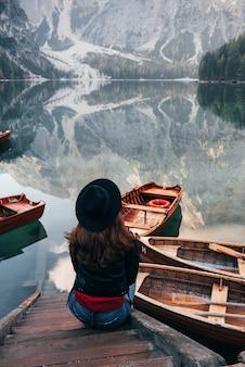 Kobieta w czarnym kapeluszu, ciesząc się majestatyczny krajobraz górski w pobliżu jeziora z łodzi