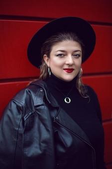 Kobieta w czarnym kapeluszu i skórzanej kurtce na czerwonej ścianie