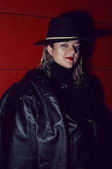 Kobieta W Czarnym Kapeluszu I Skórzanej Kurtce Na Czerwonej ścianie Premium Zdjęcia