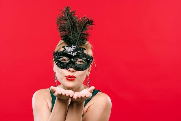 Kobieta w czarnym karnawałowym maskowym dmuchanie buziaku