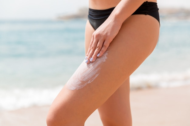 Kobieta w czarnym kostiumie kąpielowym nakłada na plażę ochronę przeciwsłoneczną palcami na nodze.