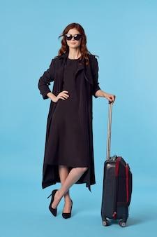 Kobieta w czarnym płaszczu bagaż lotnisko podróż na niebieskim tle podróż służbowa