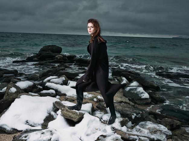 Kobieta w czarnym płaszczu na zewnątrz krajobraz ocean ciemne chmury gotyk