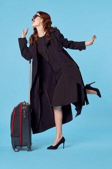 Kobieta w czarnym płaszczu walizka paszport i bilet lotniczy podróż