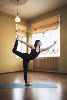 Kobieta w czarnym stroju sportowym uprawiająca jogę wykonuje natarajasanę w pozie króla tancerzy