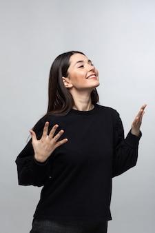 Kobieta w czarnym swetrze pokazuje radość