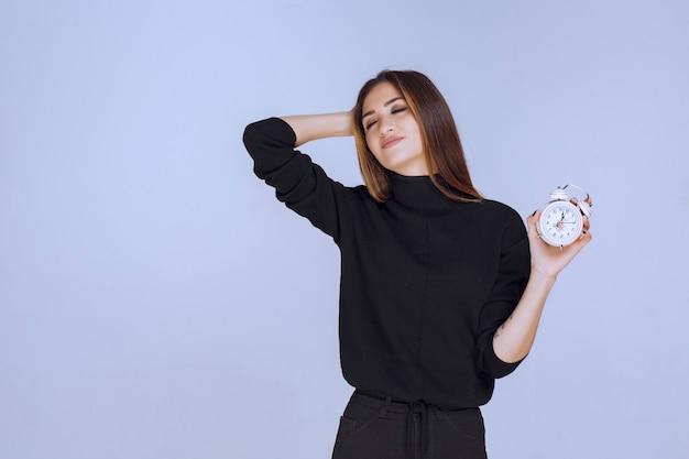 Kobieta w czarnym swetrze trzyma budzik i promuje go.