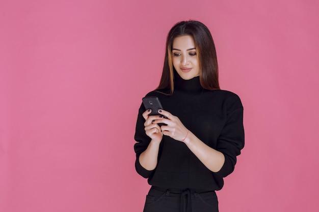 Kobieta w czarnym swetrze trzyma smartfon i pisze sms-y lub sprawdza media społecznościowe.