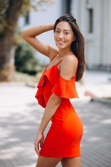 Kobieta w czerwieni sukni wzorcowy pozuje outside