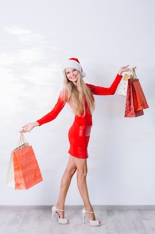Kobieta w czerwieni sukni z torba na zakupy w rękach