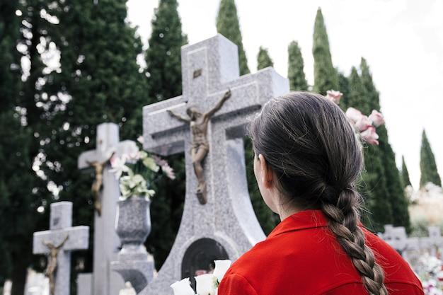 Kobieta w czerwonej bluzce i warkoczem modląca się do ukochanej osoby na cmentarzu