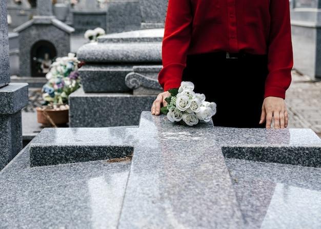 Kobieta w czerwonej bluzce składa kwiaty ukochanej osobie na cmentarzu.