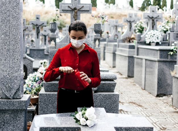 Kobieta w czerwonej bluzce zapala świecę i składa kwiaty ukochanej osobie na cmentarzu.