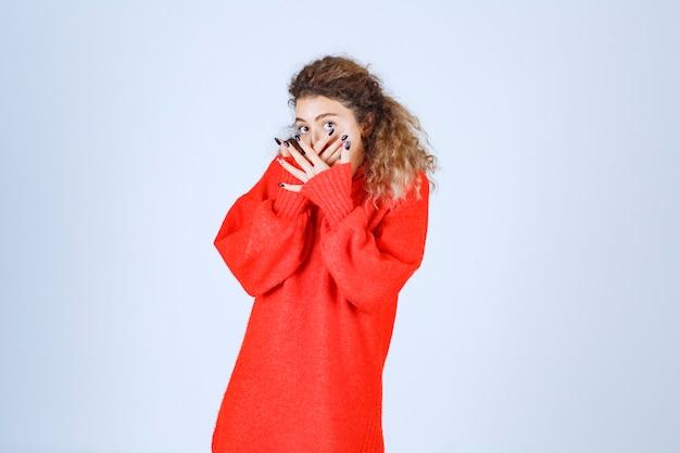 Kobieta w czerwonej bluzie patrząc przez palce.