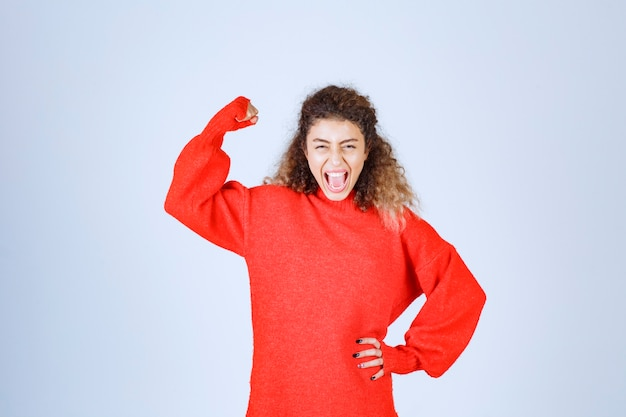 Kobieta w czerwonej bluzie pokazując pięść i oznaczającą jej moc.