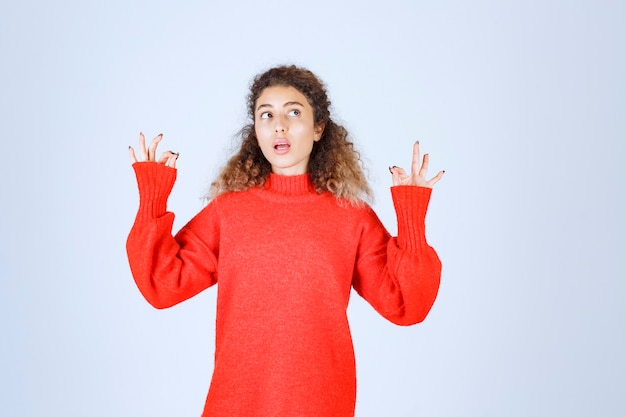 Kobieta w czerwonej bluzie pokazując znak przyjemności.