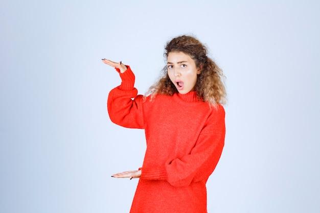 Kobieta w czerwonej bluzie pokazuje miary obiektu.