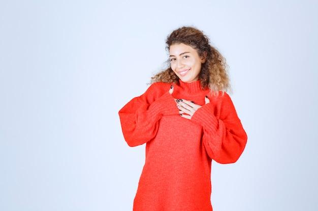 Kobieta w czerwonej bluzie, wskazując na siebie.