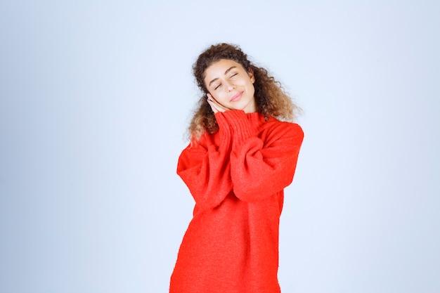 Kobieta w czerwonej bluzie wygląda na zmęczoną i senną.