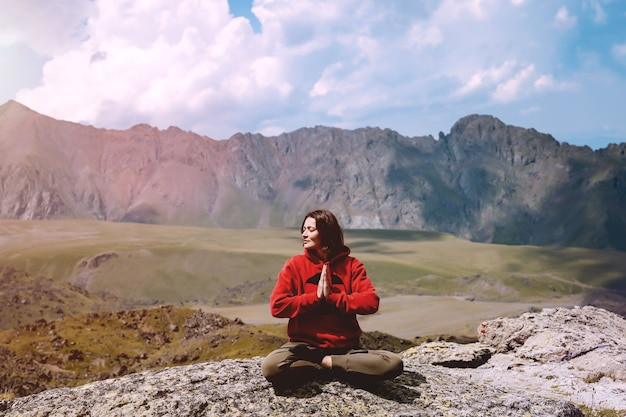 Kobieta w czerwonej bluzie z kapturem siedzi w pozycji lotosu namaste na tle gór kaukazu