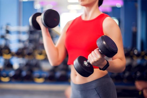 Kobieta w czerwonej górze z krótkimi blond włosami biceps szkolenia z hantlami w siłowni. koncepcja ludzie, fitness i styl życia