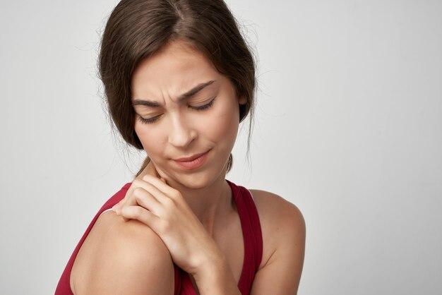 Kobieta w czerwonej koszulce ból stawów niezadowolenie problemy zdrowotne