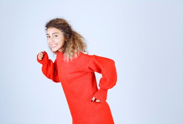 Kobieta w czerwonej koszuli działa i ucieka.