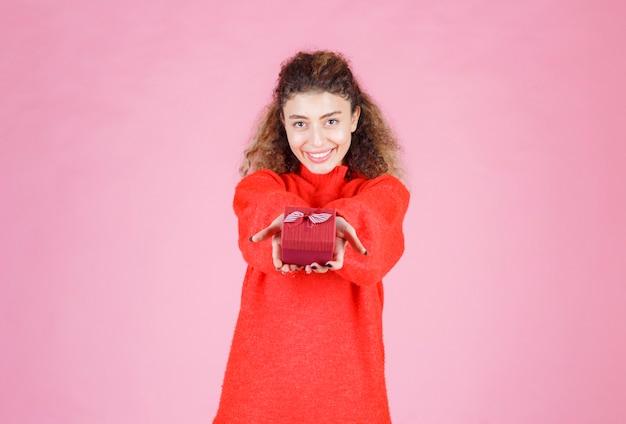 Kobieta w czerwonej koszuli oferując małe pudełko.
