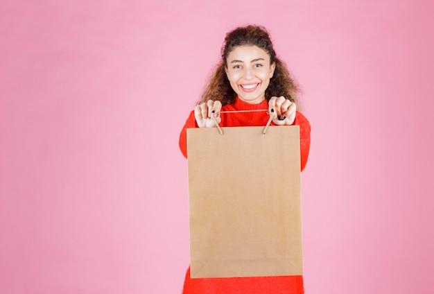 Kobieta W Czerwonej Koszuli, Oferując Przyjaciółce Kartonową Torbę Na Zakupy. Darmowe Zdjęcia