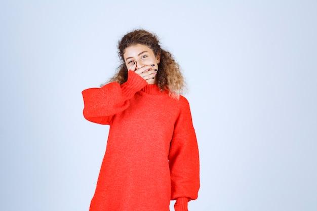 Kobieta w czerwonej koszuli patrząc przez palce i śmiejąc się.
