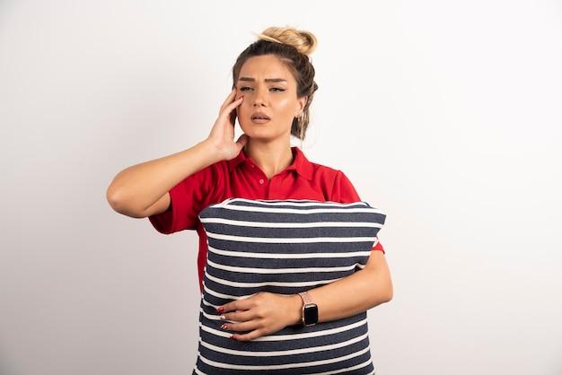 Kobieta w czerwonej koszuli przytulanie poduszkę na białym tle.