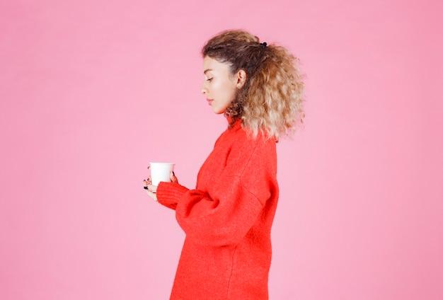 Kobieta W Czerwonej Koszuli Trzyma Filiżankę Kawy Jednorazowego Użytku. Darmowe Zdjęcia