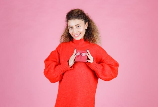 Kobieta w czerwonej koszuli trzyma małe czerwone pudełko.