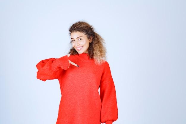Kobieta w czerwonej koszuli, wskazując na siebie.