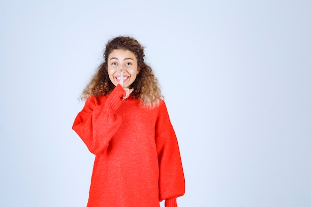 Kobieta w czerwonej koszuli, wskazując usta i prosząc o ciszę.