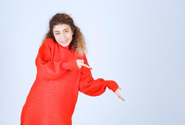 Kobieta w czerwonej koszuli wskazująca na kogoś lub gdzieś z emocjonalną twarzą na niebiesko