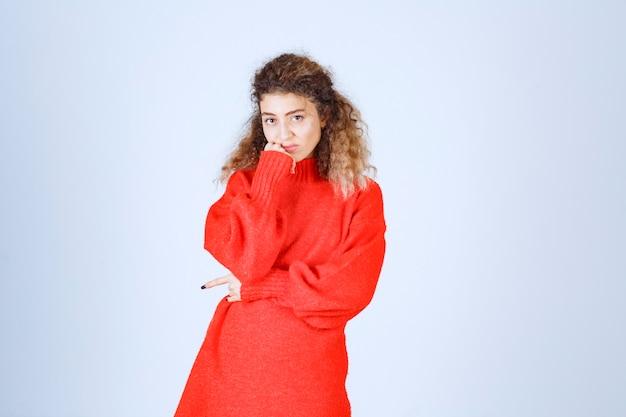 Kobieta w czerwonej koszuli wygląda pesymistycznie lub smutno.