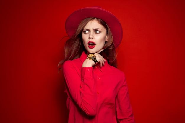 Kobieta w czerwonej koszuli z jasnym makijażem i kapeluszem