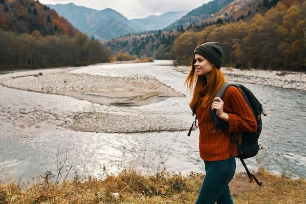 Kobieta w czerwonej kurtce i plecaku na plecach spaceruje brzegiem rzeki w