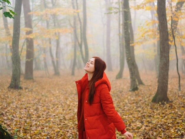 Kobieta w czerwonej kurtce jesień las natura spacer styl życia