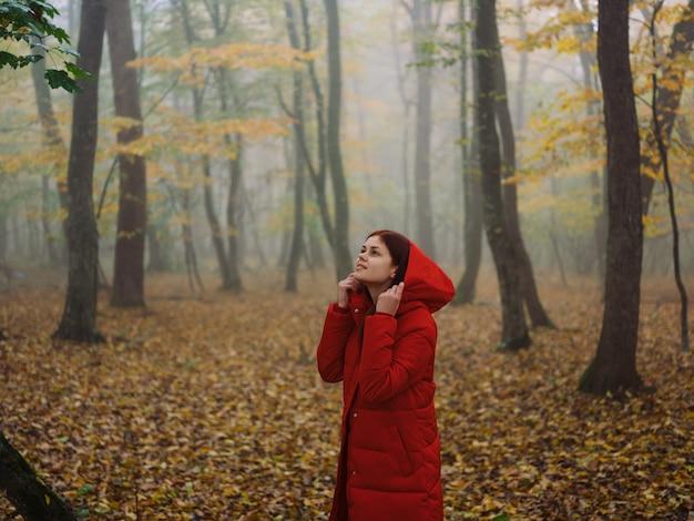 Kobieta w czerwonej kurtce jesień las natura świeże powietrze. zdjęcie wysokiej jakości