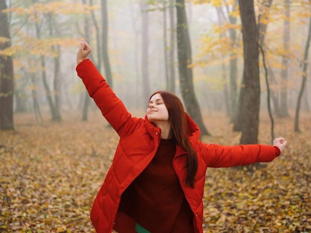 Kobieta w czerwonej kurtce jesień las świeże powietrze natura