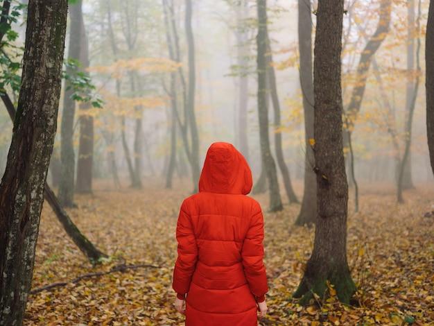 Kobieta w czerwonej kurtce jesienne liście drzewa chodzą mgłą