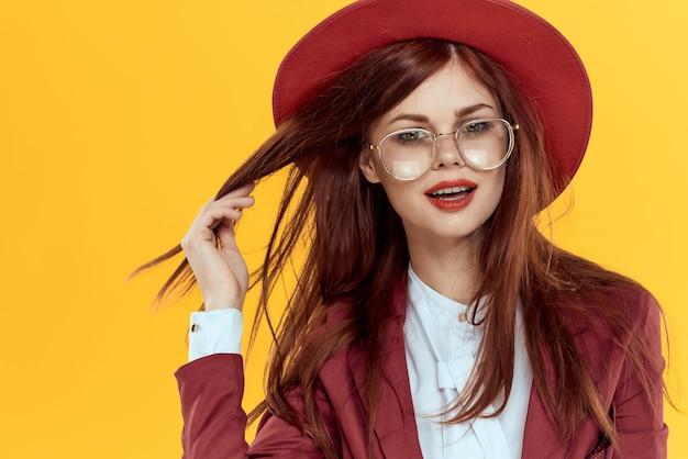 Kobieta w czerwonej kurtce kapelusz okulary żółte tło kosmetyki. wysokiej jakości zdjęcie