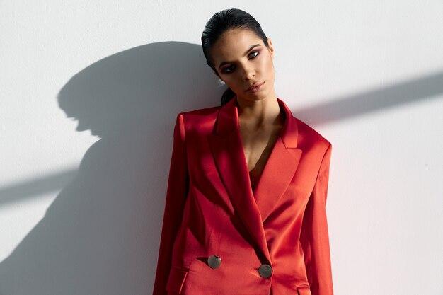Kobieta w czerwonej kurtce stoi przy ścianie wnętrza pokoju garnitur