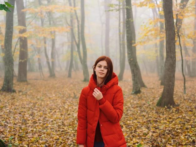 Kobieta w czerwonej kurtce w lesie w podróży przez mgłę natury
